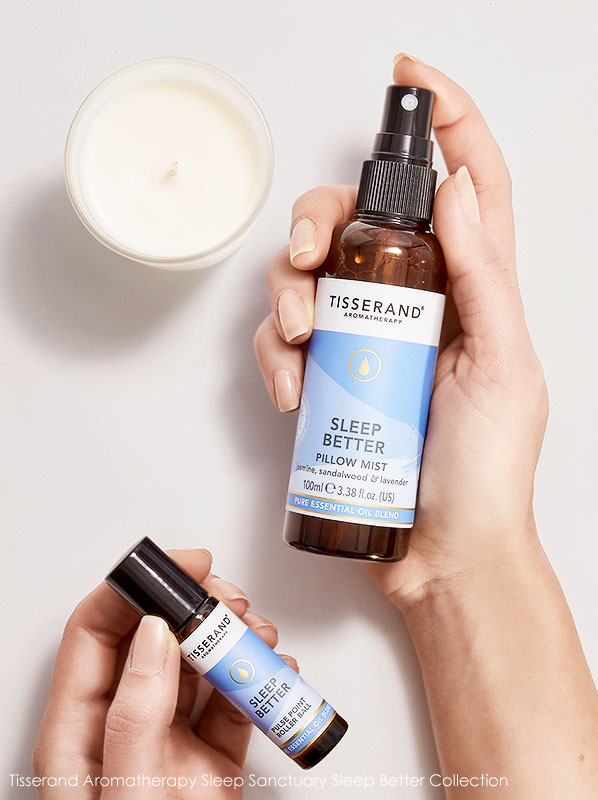 Two hands holding the Tisserand Sleep Sanctuary set pillow mist, roller ball and candle
