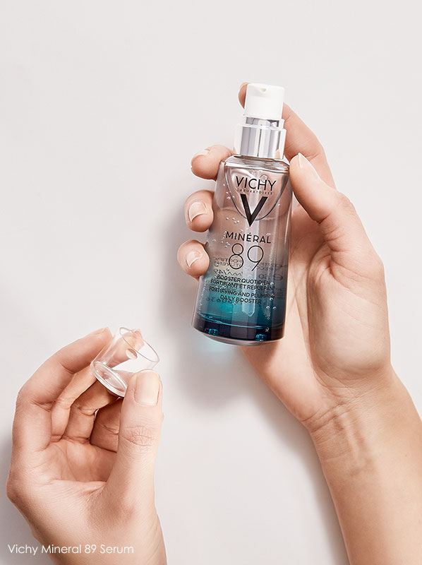 Hands holding a bottle of the Vichy Mineral 89 Serum