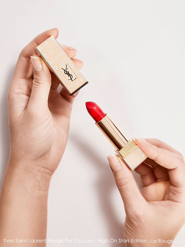 Pair of hands holding an open YSL Rouge Pur Couture Limited Edition High On Stars Lipstick in shade Le Rouge