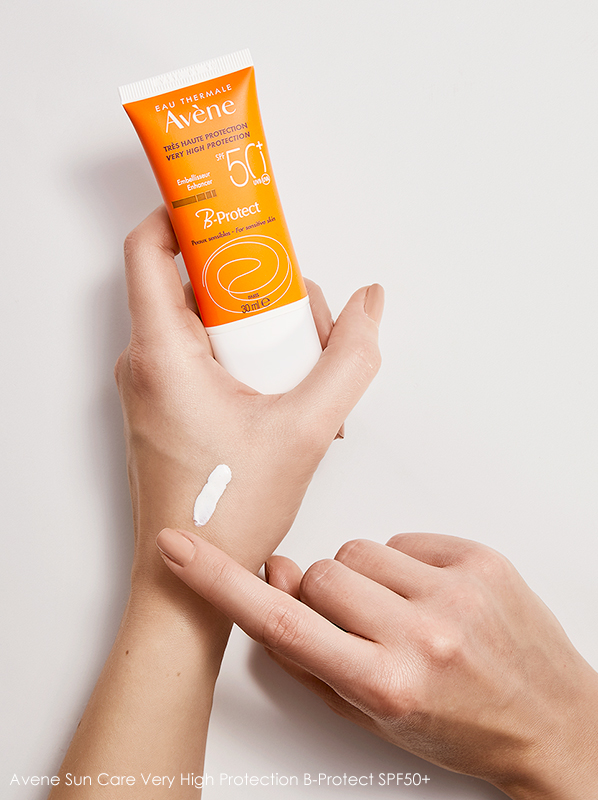 Image of model holding Avene Sun Care Very High Protection B-Protect SPF50+ and applying to the hand