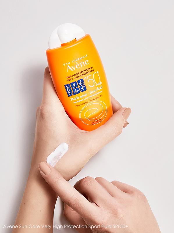 Image of model holding Avene Sun Care Very High Protection Sport Fluid SPF50+