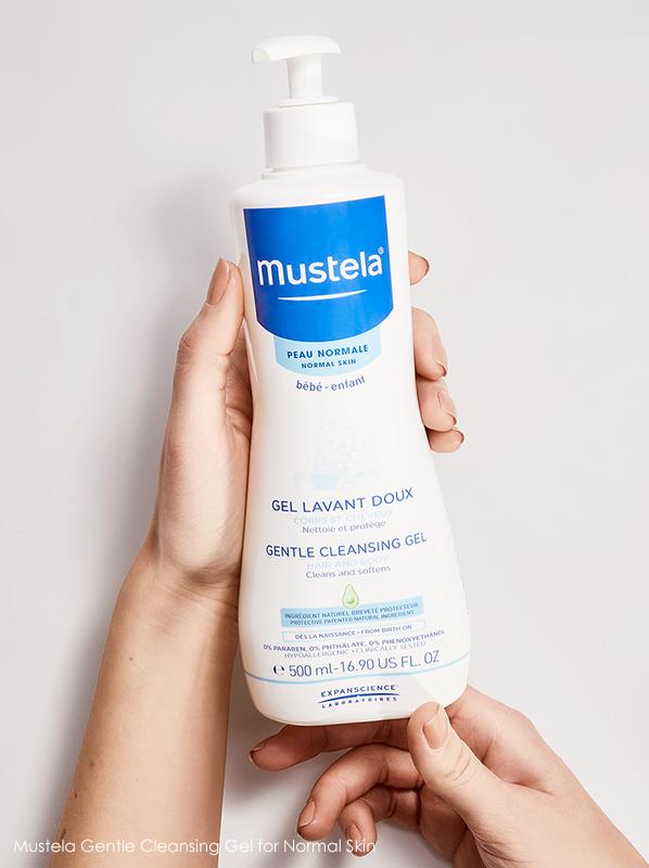 Image of model holding a bottle of Mustela Gentle Cleansing Gel for Normal Skin