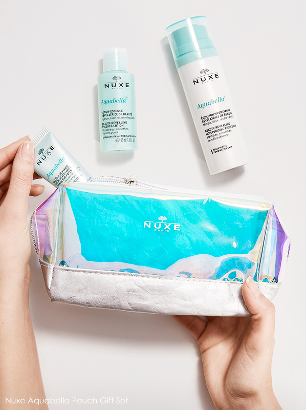 Model hand image of Nuxe Aquabella face wash, moisturiser and lotion with iridescent wash bag