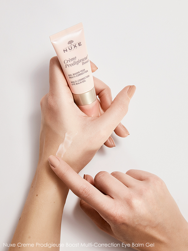 Image of model holding Nuxe Creme Prodigeuse Boost Multi-Correction Eye Balm Gel with application to hand