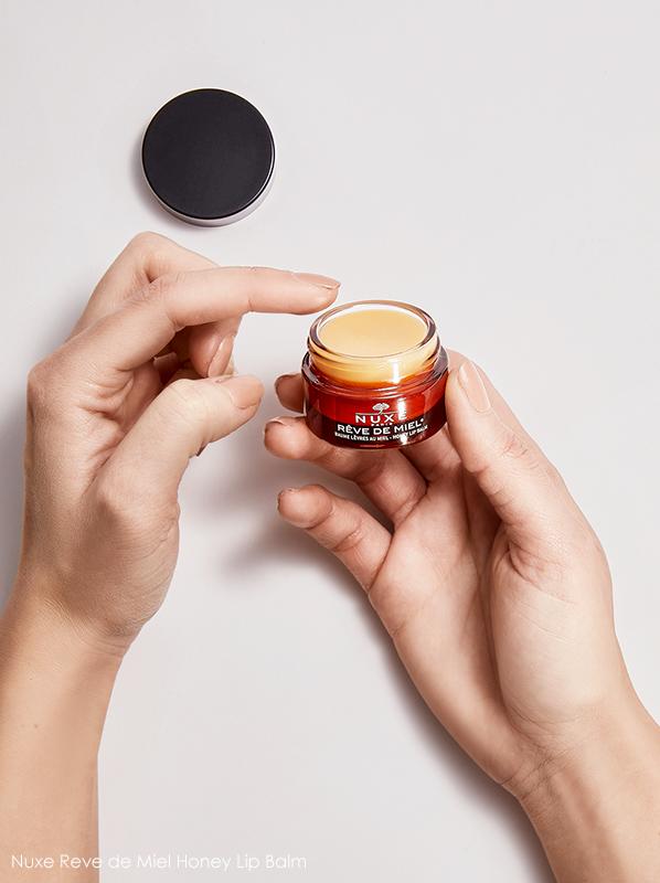 Image of model holding Nuxe Reve de Miel Honey Lip Balm 15ml - Respect Nature Collector Edition
