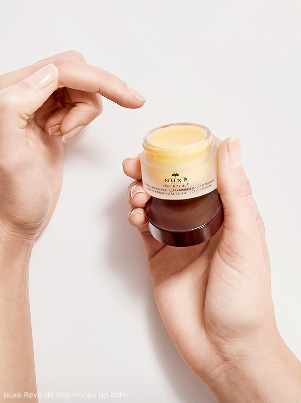 Model hand image of Nuxe Reve de miel lip balm texture