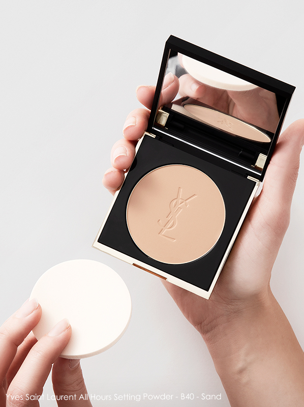 Model holding Yves Saint Laurent All Hours Setting Powder 40 Sand with powder puff