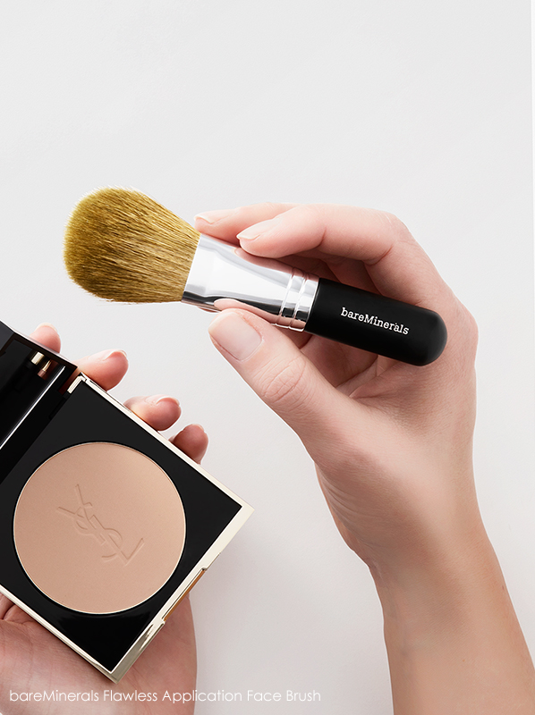 Model holding bareMinerals Flawless Application Face Brush with powder compact