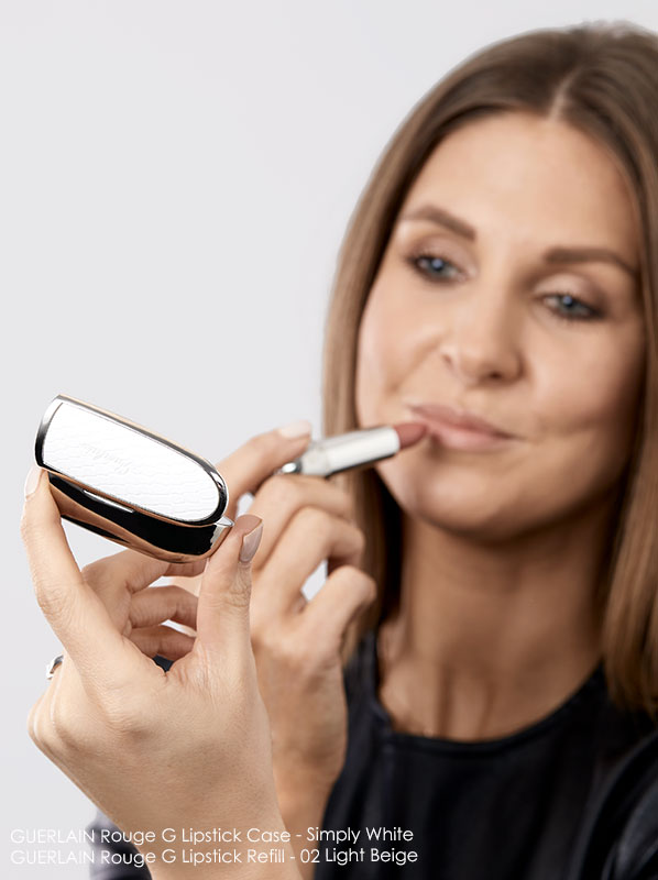 Image of model applying Guerlain Rouge G 02 Light Beige with Simply White Rouge G Lipstick Case