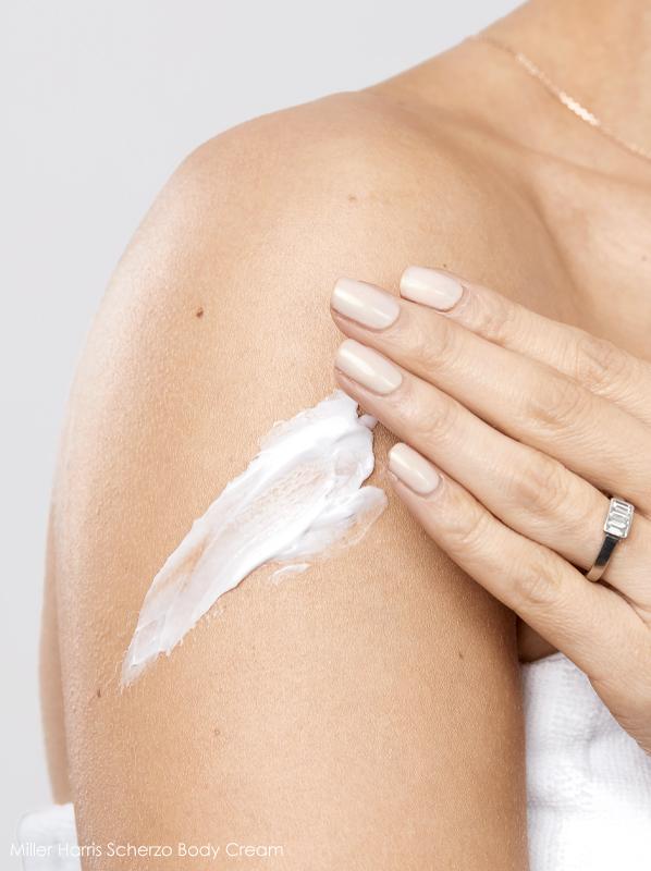 Image of model applying Miller Harris Scherzo Body Cream onto shoulder