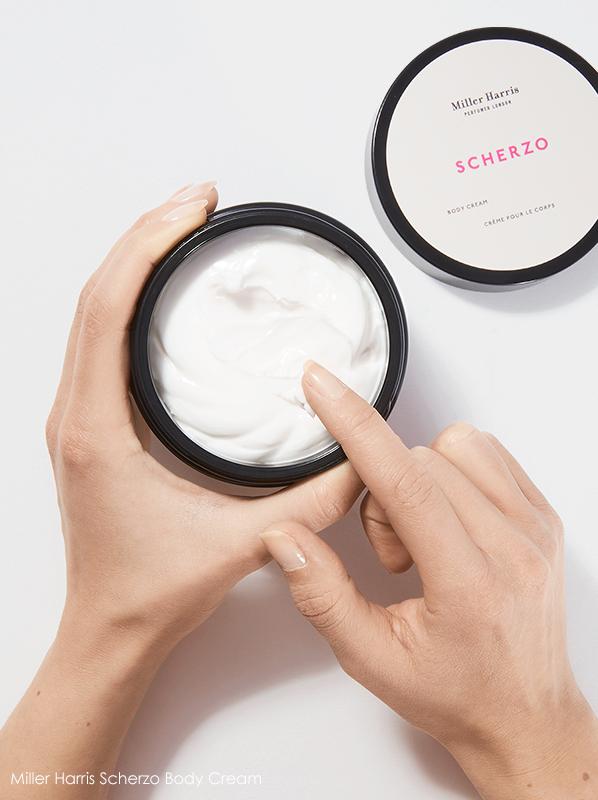Image of Miller Harris Scherzo Body Cream in hands with finger inside pot