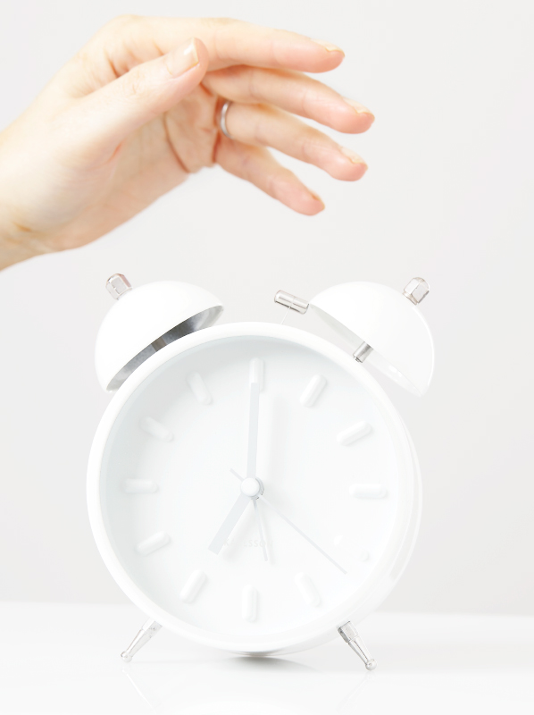 Image of white alarm clock with hand hovering over it.
