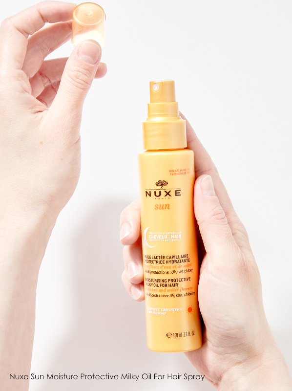 Hand image of hair spf spray Nuxe Sun Moisture Protective Milky Oil For Hair Spray