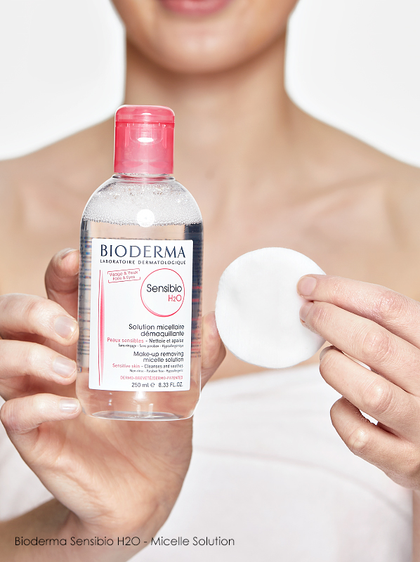 Model showing Bioderma Sensibio H2O makeup remover with a cotton pad